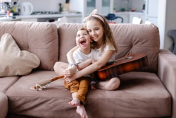 Sibling brother and sister play together. child with cerebral palsy with family in rehabilitation. Inclusion friendship with a disabled person. Music therapy playing the guitar. Sensory emotions fun