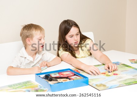 Siblings, a boy and girl play a board game on a white table against a white background