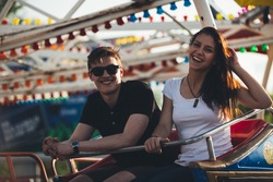 Siblings at an amusement park. Having a ride on a ferris wheel. Enjoying holidays together. Bonding concept.Friendship between opposite sexes.Best friends having fun in the summer time.