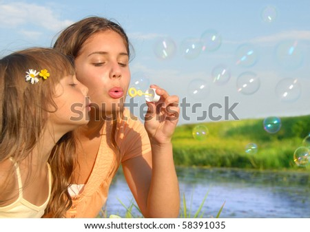 Siblings blowing soap bubbles