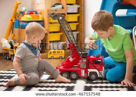 Stock Photo Siblings boys playing with a toy fire truck in kids room. Children playing cars in their room. Leisure activities at home. Playground. indoors. Profession. Fireman.