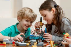 Siblings building an electronic vehicle toy using a plastic construction set, wires and soldering iron.
