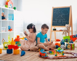Siblings children brother and sister, friends sit on the floor of the house in the children's play room with smartphones, detached from the scattered toys. Concept of new gadgets for kids.