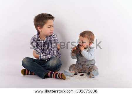 Siblings conflict and favoritism concept - Baby eating a plate of chocolate white his brother looks at him with folded arms jealousy Stockfoto ©