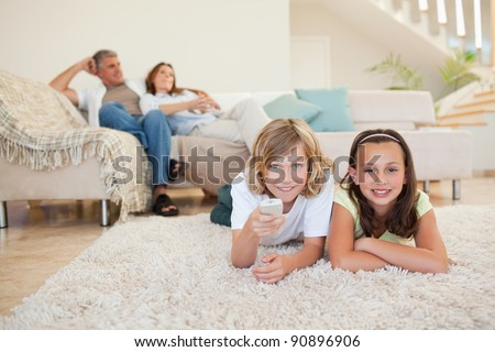 Siblings doing their homework on the floor with their parents behind them
