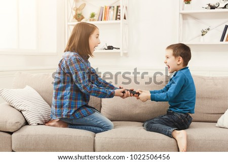 Siblings fighting over remote control at home, brother and sister have quarrel, copy space #1022506456