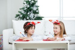 Siblings looking at each other while writing letter to Santa Claus during Christmas at home