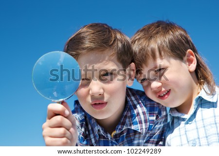 Siblings looking through magnifying glass