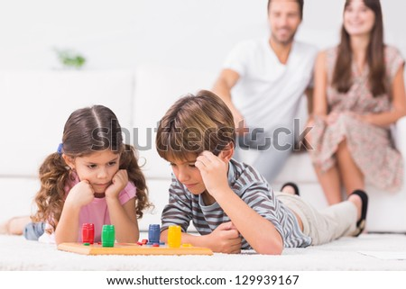 Siblings playing board game on the floor with parents sitting behind them