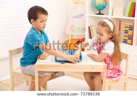 Siblings playing chess in their room sitting at the table
