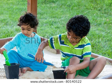 Siblings Playing in a Sand Box inside a Playset on a Summer Day