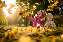 Siblings playing with maple leaves in autumn park