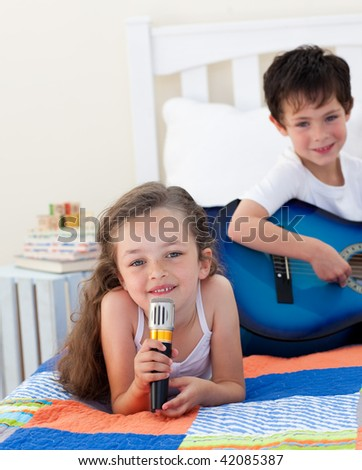 Siblings singing and playing guitar on bed