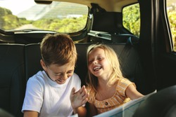 Siblings sitting on backseat of car looking at map and smiling. Kids traveling in a car on roadtrip playing with a map.