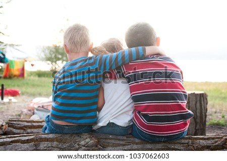 Siblings Sitting On Log With Arms Around Each Other Stock photo ©