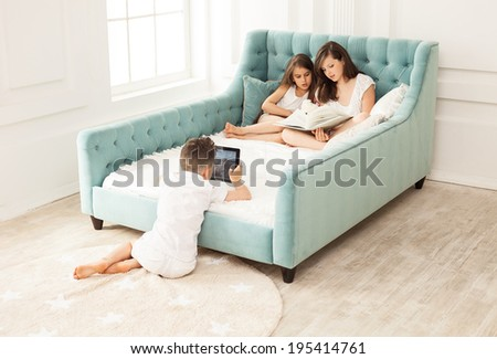 Siblings spending free time at home: two girls reading book on couch and boy using tablet while sitting on floor