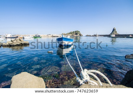 Sicilian landscape: fisher boat  with the Islands of the Cyclops on the background #747623659