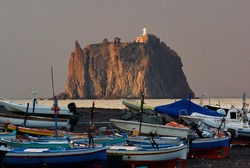 Sicily, Italy. October 26, 20012. Stromboli, volcano island in Lipari islands. Fishing boats at Ficogrande, Eastern extremity of the Island and a lighthouse on the rock near the Island.