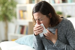 Sick adult woman coughing covering mouth with tissue sitting on a couch at home