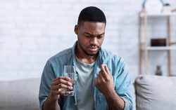 Sick African American Man Holding Pill And Glass Of Water Taking Medicine Sitting On Sofa At Home. Medication Prescription And Treatment, Side Effects Concept. Selective Focus