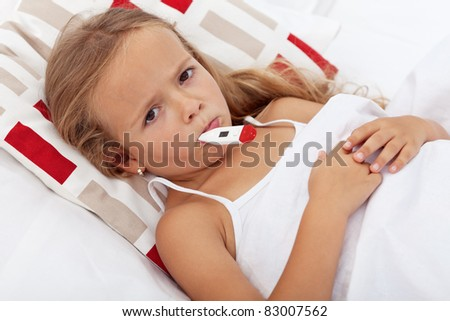 Sick and sad kid in bed holding thermometer between lips