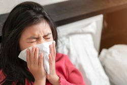 Sick asian girl have hight fever flu and sneezing into tissue on bed in bedroom, Healthcare and prevent the spread infection virus concept, Selective focus.