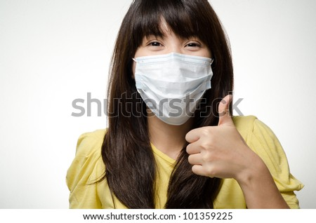 Sick asian girl on yellow shirt wear mask and do a thumb up hand