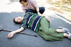 Sick asian senior woman or mother is fainted and fallen on floor,daughter help,care,support of her,elderly people unconscious lying on the ground,concept of dizziness,fainting,losing consciousness