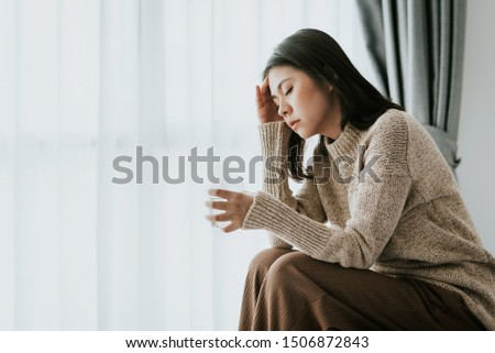 Sick Asian woman feeling  headache from flu and cold holding a glass of water, health problems treatment