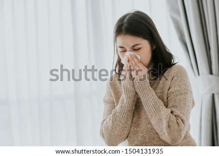 Sick Asian woman using a tissue to sneeze and blowing her nose in winter at home. Her getting sick with flu and cold.