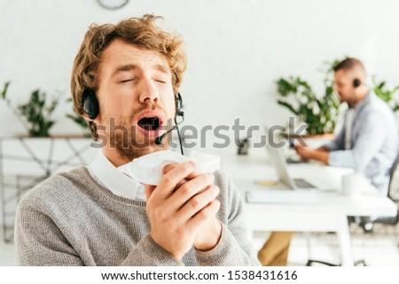 sick bearded broker with closed eyes sneezing near coworker in office