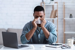 Sick Black Guy Working In Office, Sitting At Laptop And Blowing Nose In Paper Napkin Indoors. Ill Employee Concept. African Man Having Cold, Rhinitis And Sinusitis Symptoms At Work.