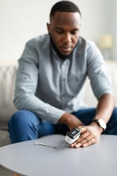 Sick Black Man Measuring Oxygen Saturation Level With Pulse Oximeter Device On Finger Sitting On Couch At Home, Selective Focus On Pulseoximeter Device. Covid-19, Ox And Pulse Rate Measurement