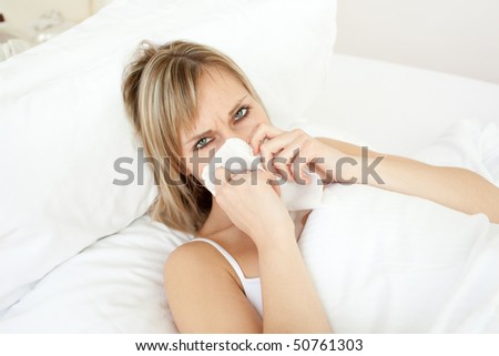 Sick blond woman blowing lying on her bed at home