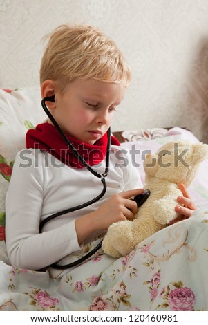 Sick boy is doing examination health for teddy bear with a stethoscope.