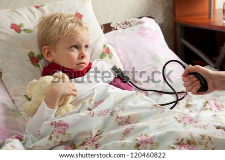Sick boy is laying in bed with his teddy bear. His blood pressure is measured tonometer.