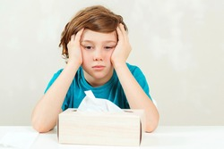Sick boy sitting at the desk. Kid using paper napkins. Allergic kid, flu season. Box with nose napkins. Boy has a virus, runny nose and headache. Schoolboy blowing runny nose.