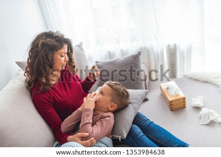 Sick boy with thermometer laying in bed and mother hand taking temperature. Mother checking temperature of her sick son.Sick child with fever and illness in bed.Mother is checking her son temperature