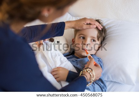 Sick boy with thermometer laying in bed and mother hand taking temperature. Mother checking temperature of her sick son who has thermometer in his mouth. Sick child with fever and illness in bed.