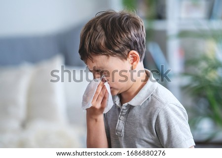 Sick caucasian boy blowing nose into tissue, Unhealthy child suffering from running nose or sneezing and covering his nose and mouth by tissue paper. period of the flu and SARS epidemic