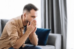 Sick caucasian guy sits on couch feel unhealthy, he suffering from rhinitis snuffles, having respiratory infection, get flue, sitting at home at quarantine