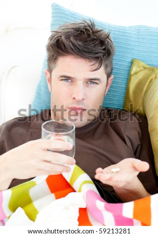 Sick caucasian man holding pills and water looking at the camera lying on the sofa