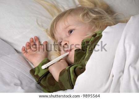 sick child in bed under blanket with thermometer in mouth