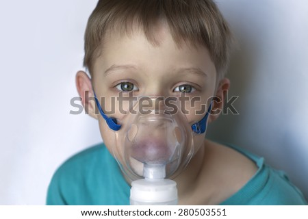 Sick child makes breathing procedure breathe through the inhaler, he looks at the camera look sick