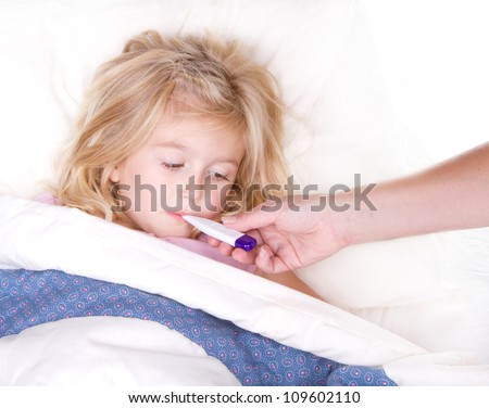 sick child with a thermometer in mouth lying in bed