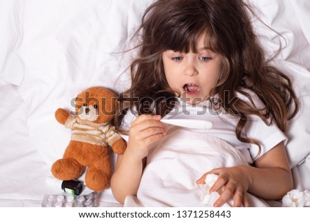 Sick child with fever and illness in bed checking temperature with thermometer. Kids flu treatments.