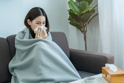 Sick, Coronavirus covid-19 asian young woman, girl headache under blanket have a fever, flu and use tissues paper sneezing nose, runny sitting on sofa bed at home. Health care on virus person.
