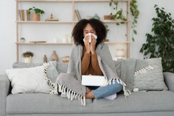 Sick day at home, treatment, unhealthy african american millennial woman has runny nose, cough and cold. Portrait of beautiful lady caught flu Illness covered with blanket on couch with napkins