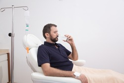 Sick, dehydrated or hangover patient man receiving vitamin IV infusion drip and drinking glass of water in hospital or beauty salon. Healthcare and medicine concept