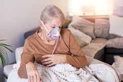Sick elderly woman making inhalation, medicine is the best medicine. Ill senior woman wearing an oxygen mask and undergoing treatment. Senior woman with an inhaler